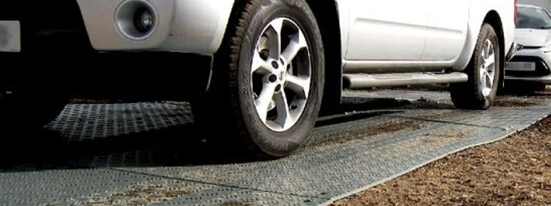 Car driving on ground protection mats