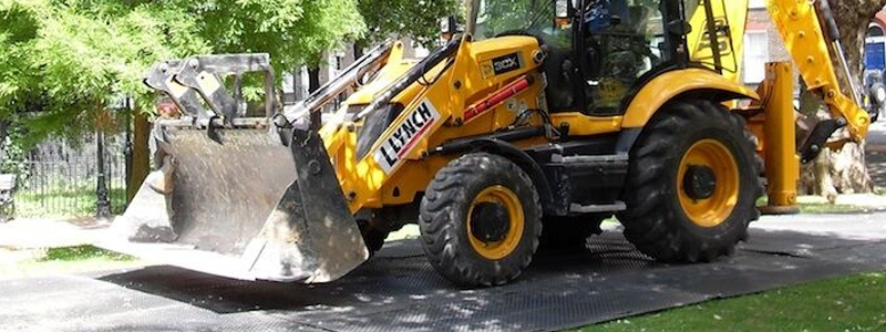 Digger driving on ground protection mats