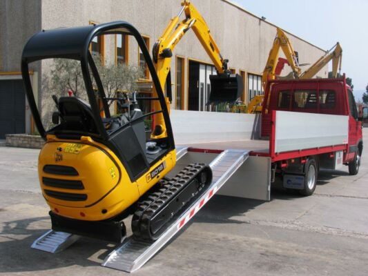 Mini digger loading in to tipper truck on loading ramps
