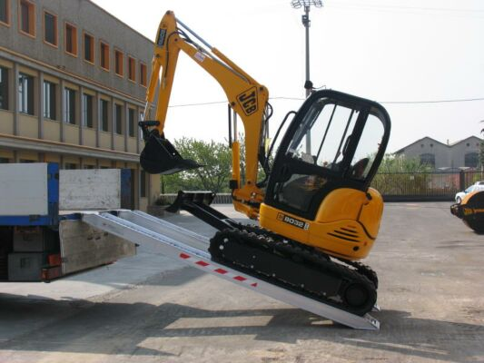 Mini digger driving on loading ramps